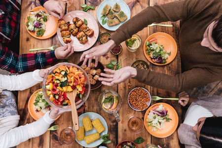 Photo pour Friends having dinner. Top view of four people having dinner together while sitting at the rustic wooden table - image libre de droit
