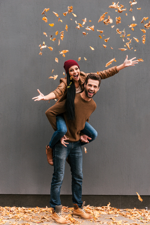 Photo for Autumn fun. Full length of handsome young man piggybacking his girlfriend throwing orange fallen leaves an smiling with grey wall as background - Royalty Free Image