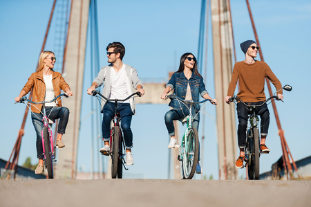 Foto de Spending carefree time together. Four young people riding bicycles along the bridge and smiling - Imagen libre de derechos