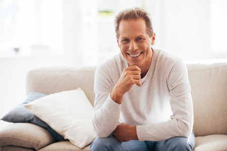 Photo pour He got candid smile. Cheerful mature holding hand on chin and looking at camera while sitting on the couch at home - image libre de droit