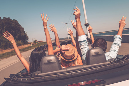 Photo pour Enjoying road trip. Rear view of young happy people enjoying road trip in their convertible and raising their arms up - image libre de droit