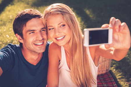 We love selfie! Happy young loving couple making selfie and smiling while sitting together on the grass in park