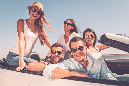 Foto de Spending great time together. Group of young happy people enjoying road trip in their white convertible and smiling at camera - Imagen libre de derechos