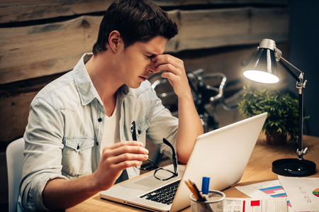 Photo pour Feeling exhausted. Frustrated young man keeping eyes closed and looking tired while working late at his working place - image libre de droit