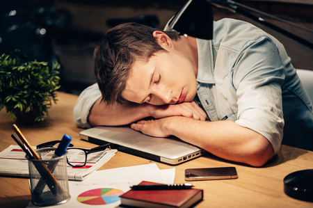 Photo pour Too much work. Young man sleeping at his working place while leaning his head on the laptop - image libre de droit