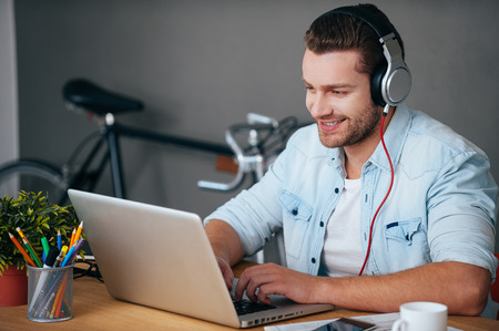 Foto de Enjoying work and good music. Cheerful young man in headphones listening to the music while sitting at his working place with bicycle standing in the background - Imagen libre de derechos