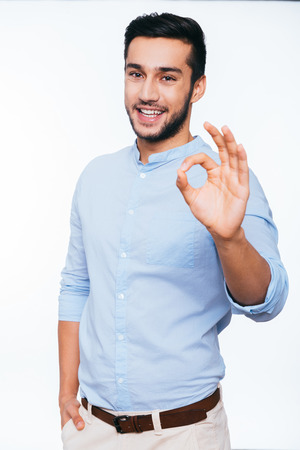 Photo for Everything is OK! Confident young Indian man gesturing OK sign and smiling while standing against white background - Royalty Free Image