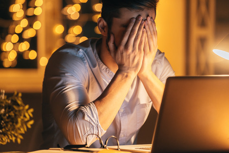 Photo pour Feeling sick and tired. Frustrated young man covering face with hands while sitting at his working place at night time with Christmas lights in the background - image libre de droit