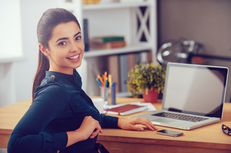 Photo pour Enjoying her working day. Attractive young woman looking over shoulder and smiling while sitting at her working place in office - image libre de droit
