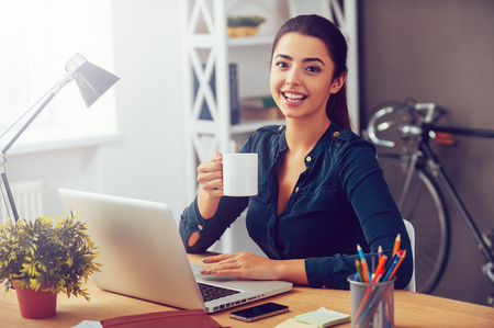 Photo for Coffee break. Attractive young woman holding coffee cup and smiling while sitting at her working place in office - Royalty Free Image