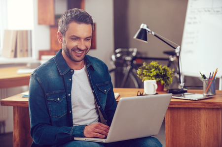 Photo for Surfing the net in office. Confident young man working on laptop and smiling while sitting at his working place in office - Royalty Free Image
