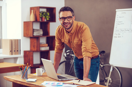 Photo for Confident and successful. Handsome young man looking at camera and smiling while standing near his working place in office - Royalty Free Image