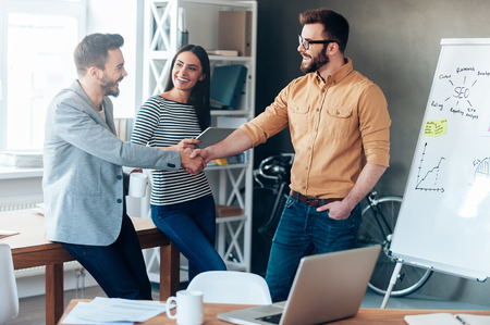 Foto per Good job! Confident young man standing near whiteboard and shaking hand to his colleague while young woman standing near them and smiling - Immagine Royalty Free