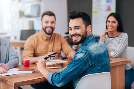 Photo pour Enjoying good working day together. Group of confident business people in smart casual wear sitting at the table and smiling - image libre de droit
