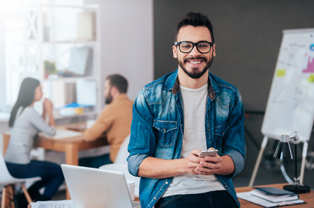 Photo for Full of new great ideas. Confident young man holding smart phone and looking at camera with smile while his colleagues working in the background - Royalty Free Image