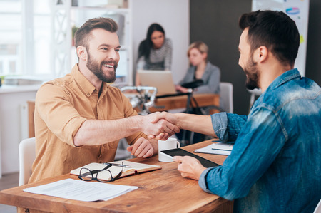Photo for Well done! Two confident young men shaking hands and smiling while sitting at the desk in office with two people working in the background - Royalty Free Image