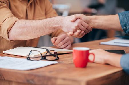 Foto de Sealing a deal. Close-up of two men shaking hands while sitting at the wooden desk - Imagen libre de derechos