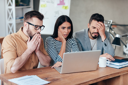 Foto de Oh no! Three frustrated young business people in smart casual wear looking at the laptop and expressing negativity - Imagen libre de derechos