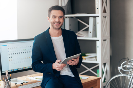 Foto de Confident business expert. Confident young man holding digital tablet and smiling while leaning at the deck in office - Imagen libre de derechos