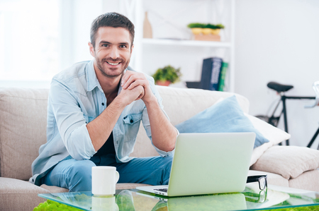 Photo for Enjoying time at home. Handsome young man looking at camera and smiling while sitting on the couch at home with laptop laying near him - Royalty Free Image
