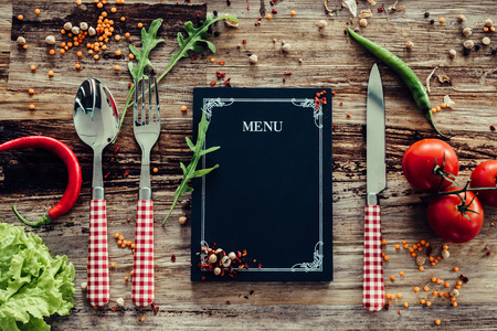 Photo for Restaurant menu. Top view of chalkboard menu laying on the rustic wooden desk with vegetables around - Royalty Free Image