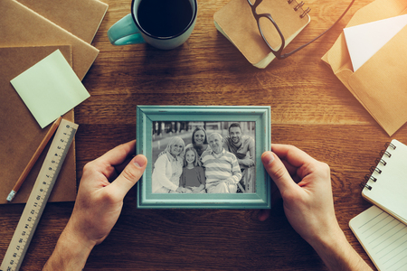 Photo for My family is my inspiration. Close-up top view of man holding photograph of his family over wooden desk with different chancellery stuff laying around - Royalty Free Image