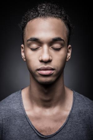 Foto de Calm and confident. Portrait of young African man keeping eyes closed while standing against black background - Imagen libre de derechos