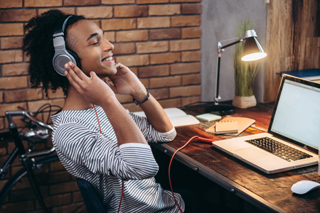 Photo for His favorite song. Side view of cheerful young African man adjusting headphones and keeping eyes closed while sitting at his working place - Royalty Free Image
