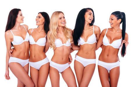 Photo pour Carefree beauties. Group of cheerful women in lingerie embracing and looking at each other while standing against white background - image libre de droit