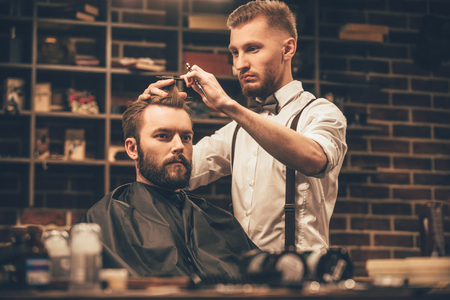 Photo pour Making haircut look perfect. Young bearded man getting haircut by hairdresser while sitting in chair at barbershop - image libre de droit