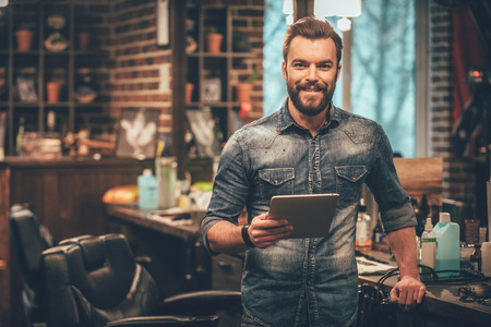 Foto de Keeping business on top with digital technologies. Cheerful young bearded man looking at camera and holding digital tablet while standing at barbershop - Imagen libre de derechos