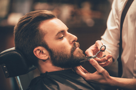 Foto de Getting perfect shape. Close-up side view of young bearded man getting beard haircut by hairdresser at barbershop - Imagen libre de derechos