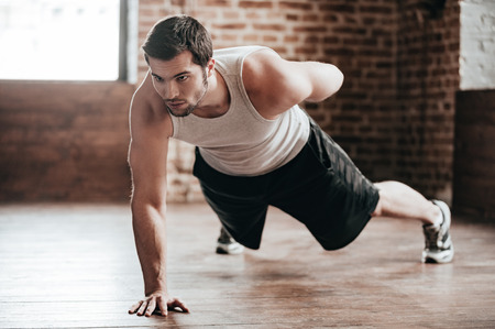 Photo for One hand push-up. Confident muscled young man wearing sport wear and doing one hand push-up while exercising on the floor in loft interior - Royalty Free Image