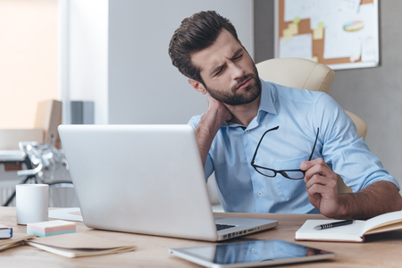 Foto de Feeling exhausted. Frustrated young handsome man looking exhausted while sitting at his working place and carrying his glasses in hand - Imagen libre de derechos
