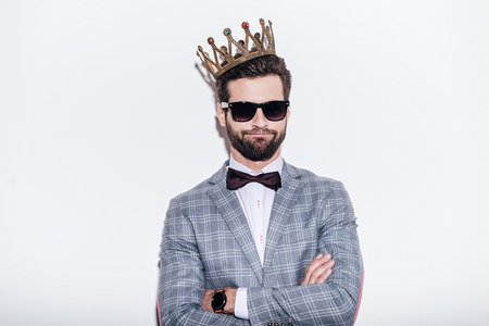Photo pour King of style. Sneering young handsome man wearing suit and crown keeping arms crossed and looking at camera while standing against white background - image libre de droit
