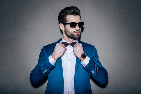 Photo for Mr. Perfection. Close-up of handsome young man wearing sunglasses adjusting his bow tie and looking away while standing against grey background - Royalty Free Image