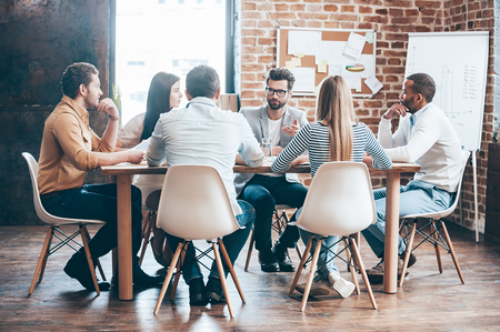 Photo for Morning meeting. Group of six young people discussing something while sitting at the table in office together - Royalty Free Image