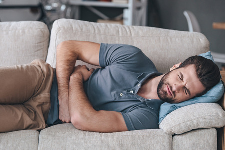 Photo for Terrible stomachache. Frustrated handsome young man hugging his belly and keeping eyes closed while lying on the couch at home - Royalty Free Image