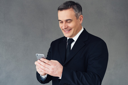 Great business news! Mature businessman using smartphone with smile while standing against grey background