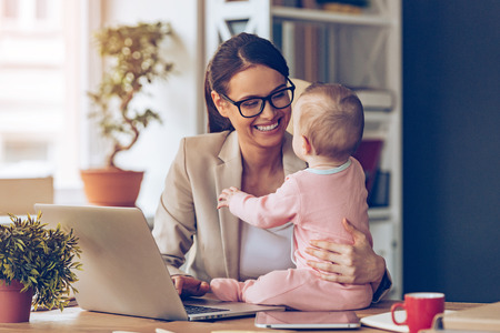 Foto de Working together is so fun! Cheerful young beautiful businesswoman looking at her baby girl with smile while sitting at her working place - Imagen libre de derechos