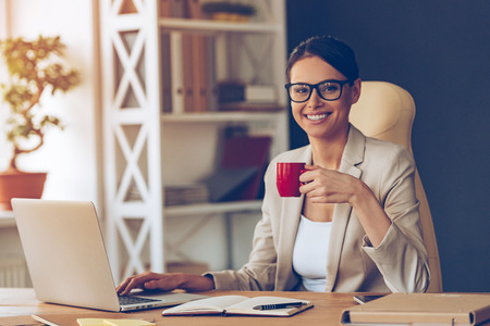 Photo pour Beautiful expertise. Cheerful young beautiful businesswoman in glasses holding coffee cup and looking at camera with smile while sitting at her working place - image libre de droit