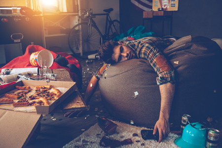 Foto de Young handsome man passed out on bean bag with joystick in his hand in messy room after party - Imagen libre de derechos