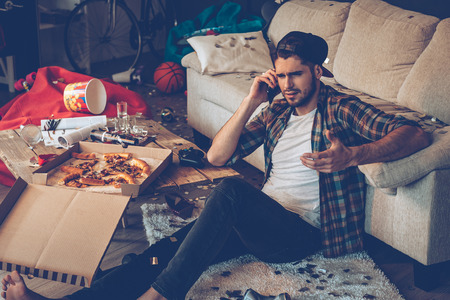 Foto de Handsome young man talking on mobile phone and gesturing while sitting on the floor in messy room after party - Imagen libre de derechos