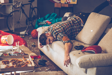 Foto de Young handsome man passed out on sofa in messy room after party - Imagen libre de derechos