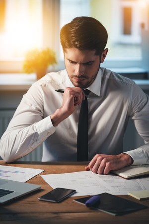 Photo for Pensive young handsome man looking at documents and keeping hand on chin while sitting at his working place - Royalty Free Image