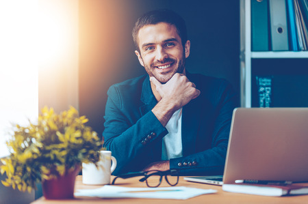 Photo pour Confident and handsome. Confident young man holding hand on chin and smiling while sitting at his working place in office - image libre de droit