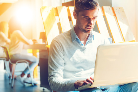 Photo for Concentrated on work. Concentrated young man working on laptop while his colleagues working in the background - Royalty Free Image