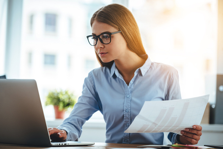 Photo for Double-checking everything. Young beautiful woman in glasses using laptop and holding documents while sitting at her working place - Royalty Free Image