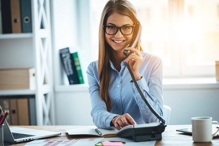 Foto de I will connect you in one second! Cheerful young beautiful woman in glasses talking on the phone and looking at camera with smile while sitting at her working place - Imagen libre de derechos