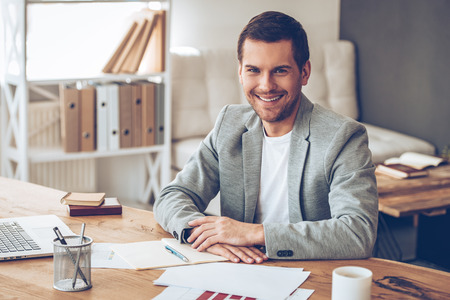 Photo for Casual business day. Cheerful handsome young man looking at camera with smile while sitting at his working place - Royalty Free Image